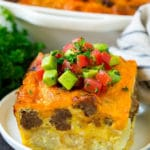 A slice of sausage egg casserole with a garnish of fresh tomatoes.