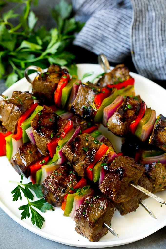 Shish kabob made with beef, peppers and onions on a serving plate.