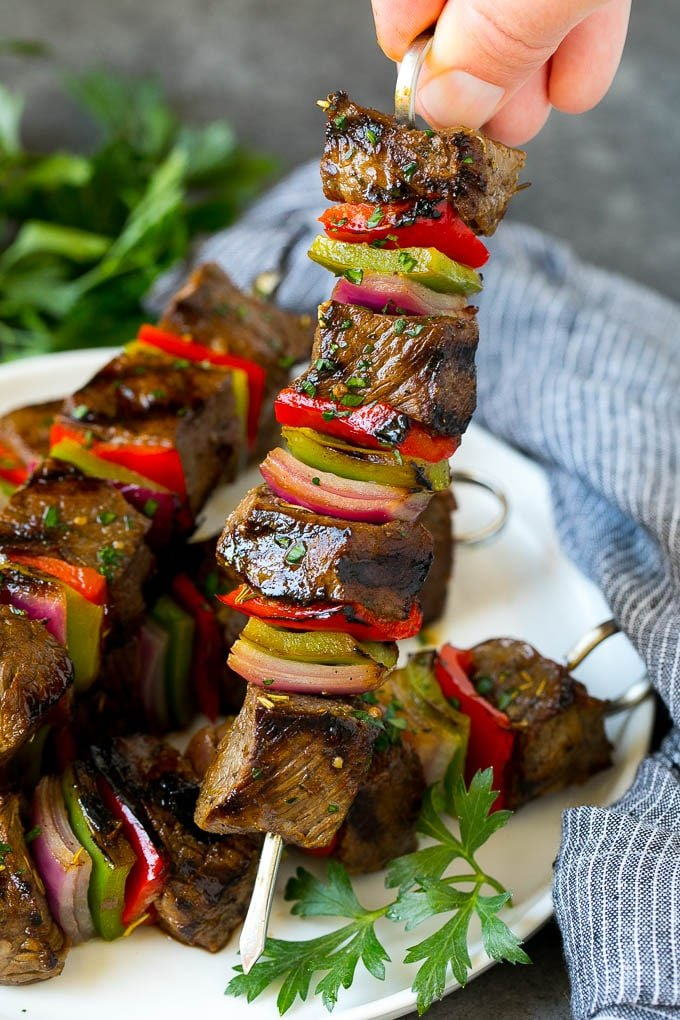 A hand holding a beef shish kabob with peppers and onions.