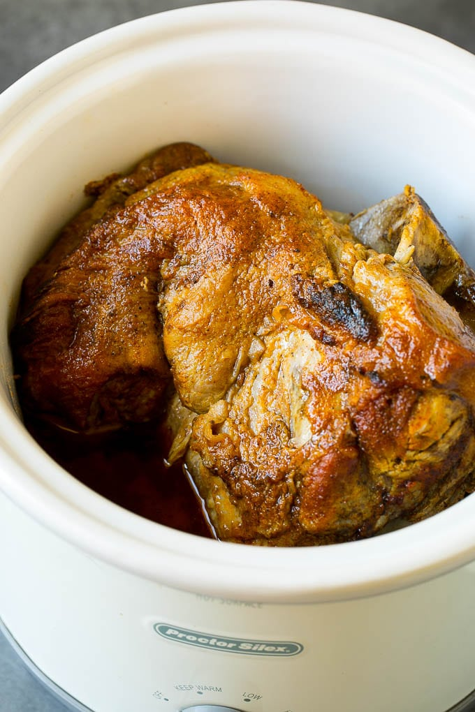 A pork roast inside of a crock pot.