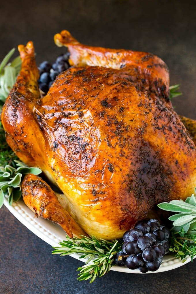 A whole roasted Thanksgiving turkey on a platter that's decorated with grapes and herbs.