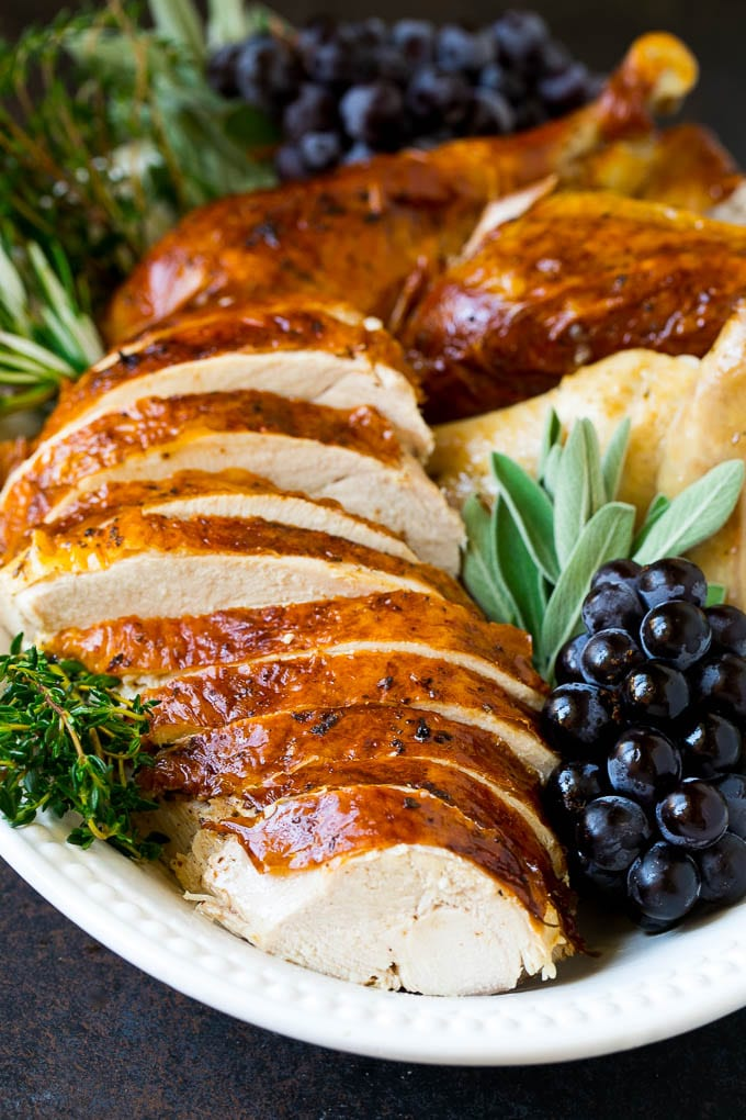 Sliced Thanksgiving turkey on a serving platter with fresh herbs.