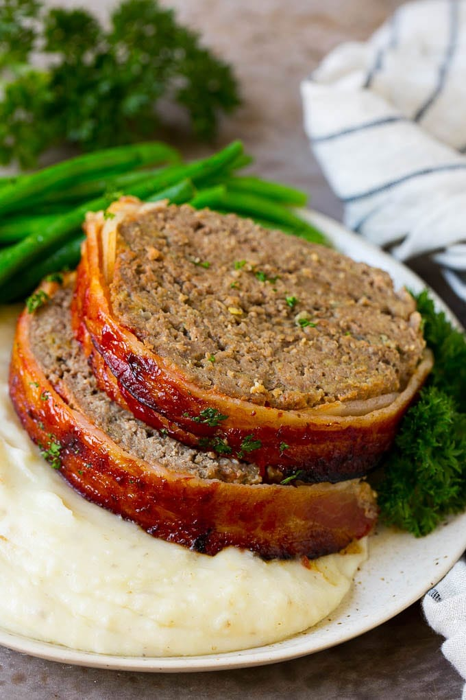 Slices of bacon wrapped meatloaf served over mashed potatoes with green beans.