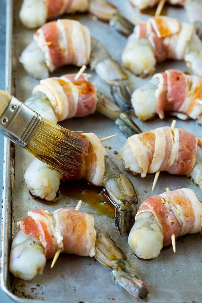 A basting brush applying sauce to shrimp.