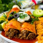 A plate of beef enchiladas topped with sour cream, olives and green onions.