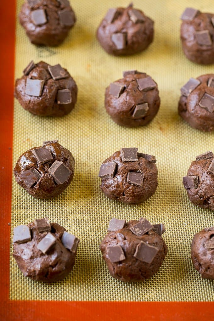 Balls of cookie dough with chocolate pieces pressed into the tops.