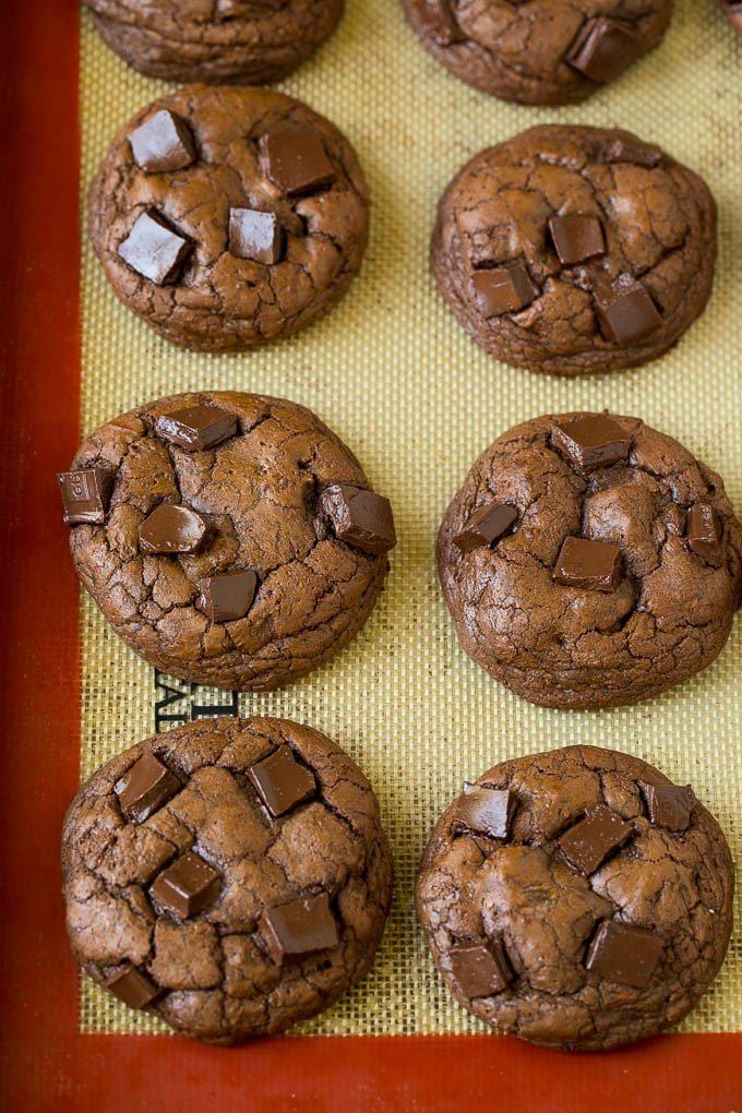 Baked chocolate cookies on a sheet pan.