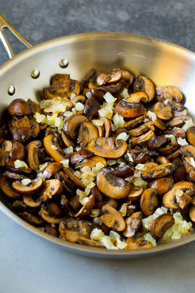 Sauteed mushrooms and onions in a skillet.