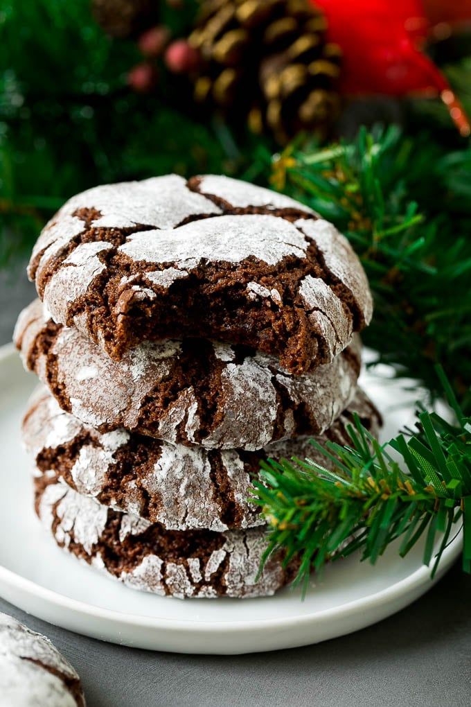 A stack of chocolate crinkle cookies with a bite taken out of one.