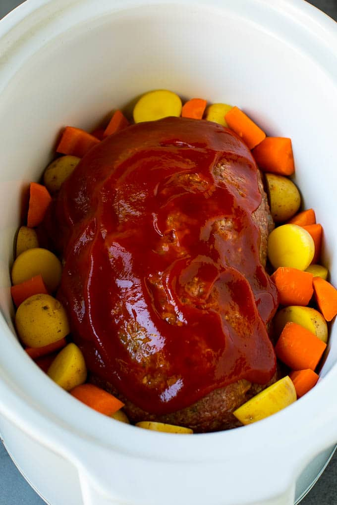 A loaf of ground beef topped with ketchup in a slow cooker, surrounded by carrots and potatoes.