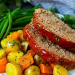 Slices of crockpot meatloaf served with carrots, potatoes and green beans.