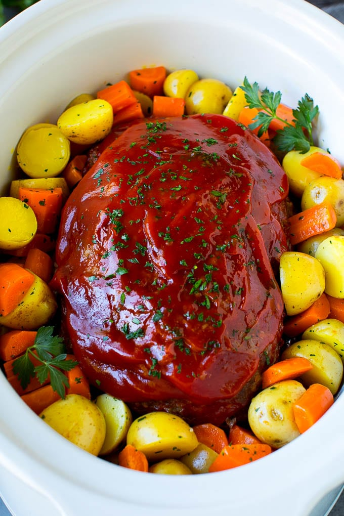 Crockpot meatloaf topped with ketchup and surrounded by carrots and potatoes.