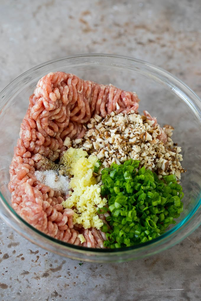 Ground pork with diced mushrooms and seasonings in a mixing bowl.