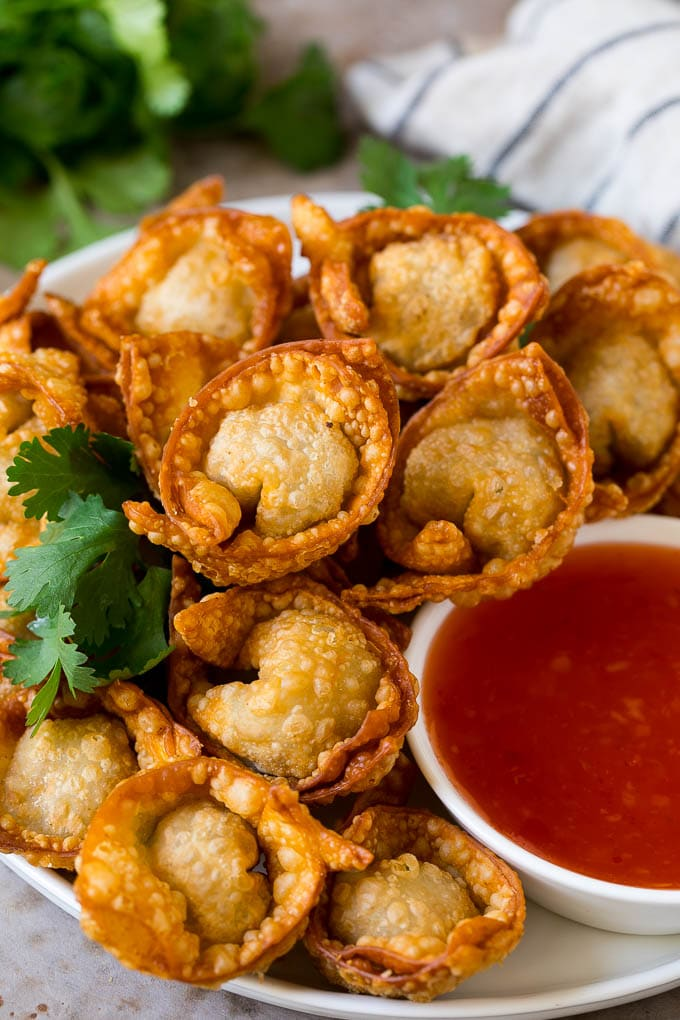 A plate of fried wonton served with sweet chili sauce.