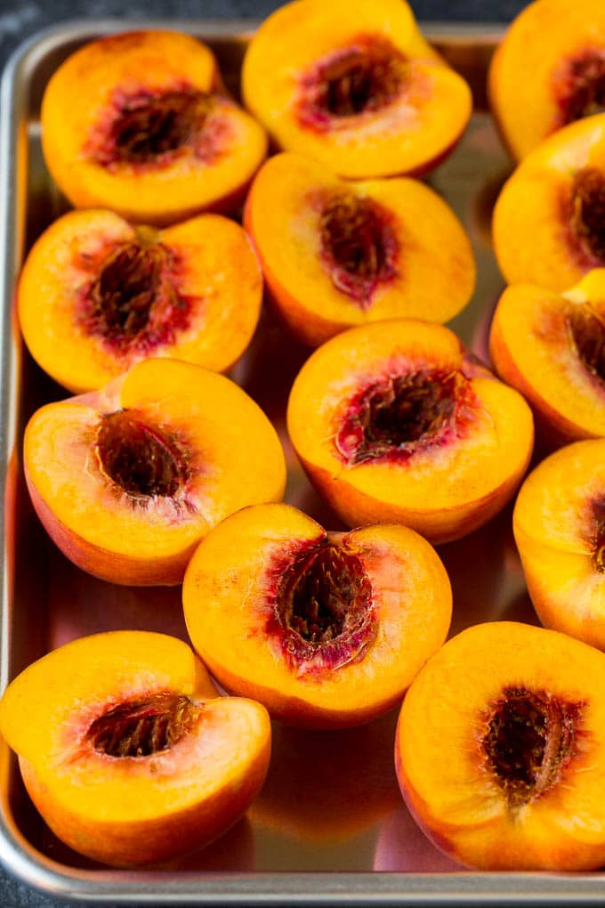 Peaches cut in half on a sheet pan.