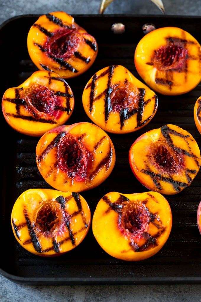 Peach halves cooked on a grill pan.