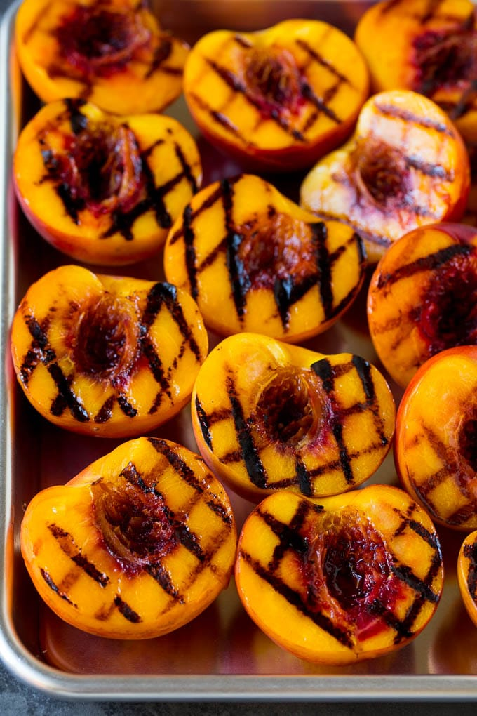 Grilled peach halves arranged on a tray.