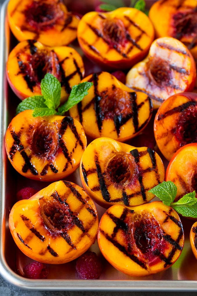 Grilled peaches garnished with raspberries and fresh mint.