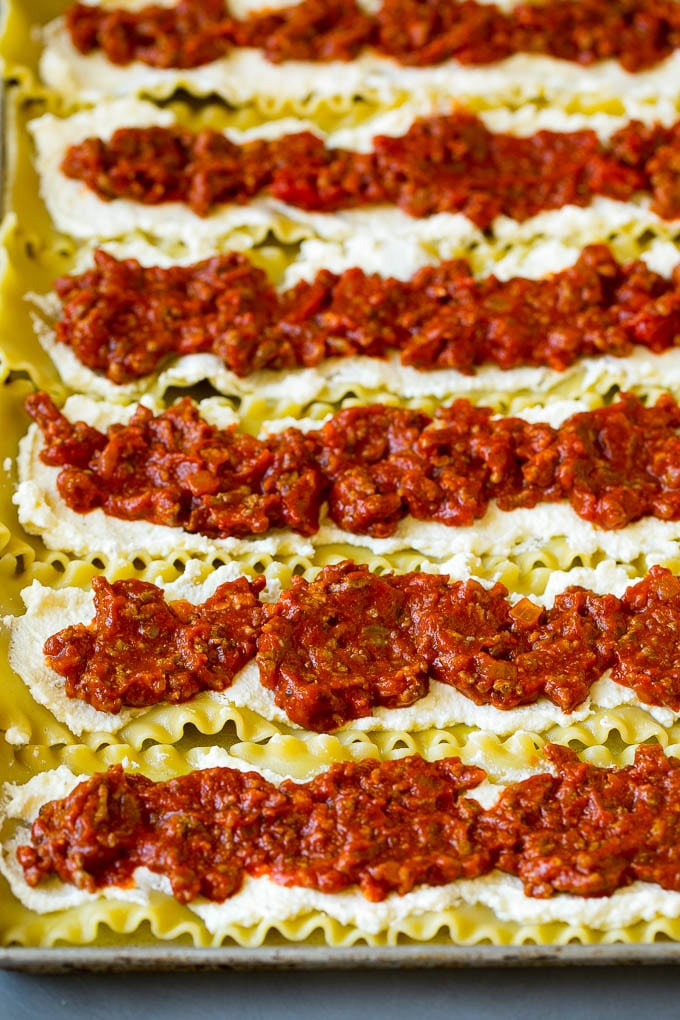 Lasagna noodles topped with ricotta and meat sauce.