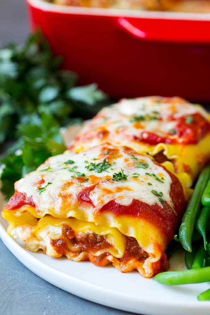 Lasagna roll ups with meat sauce, served with a side of green beans.