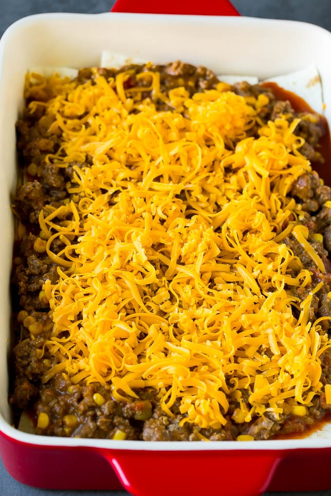 Layers of tortillas, ground beef and shredded cheese in a baking dish.