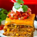 A slice of Mexican lasagna made with layers of cheese, tortillas and meat.