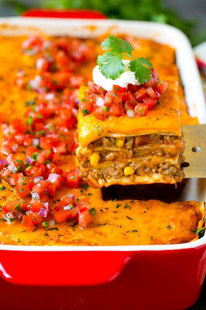 A spatula serving up a portion of Mexican lasagna.