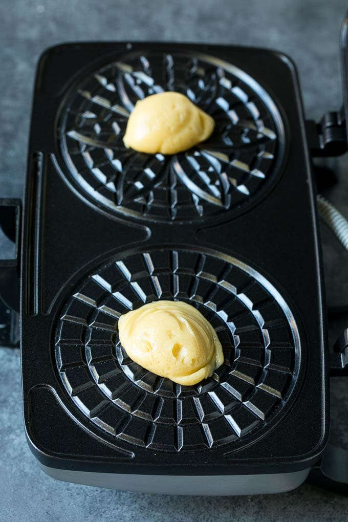 Dollops of dough in a cookie iron.