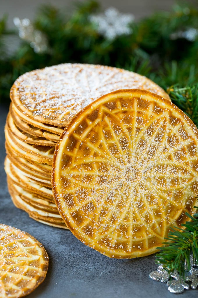 A stack of pizzelle cookies dusted with powdered sugar.