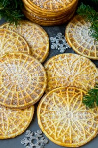 Pizzelle cookies cooked to golden brown and coated in powdered sugar.