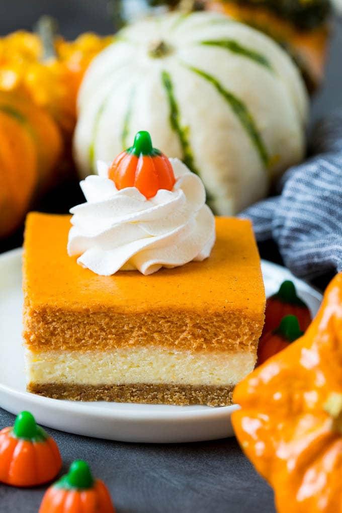Pumpkin cheesecake bars garnished with whipped cream.