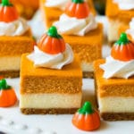 A platter of pumpkin cheesecake bars topped with whipped cream and candy pumpkins.