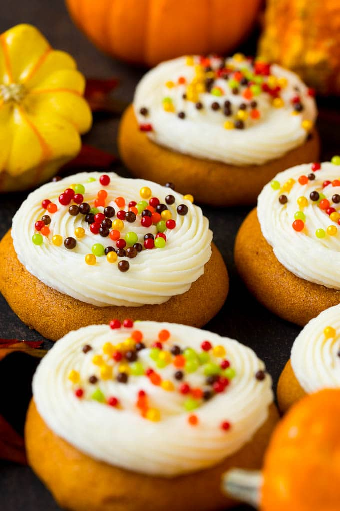 Pumpkin cookies topped with cream cheese frosting and fall sprinkles.