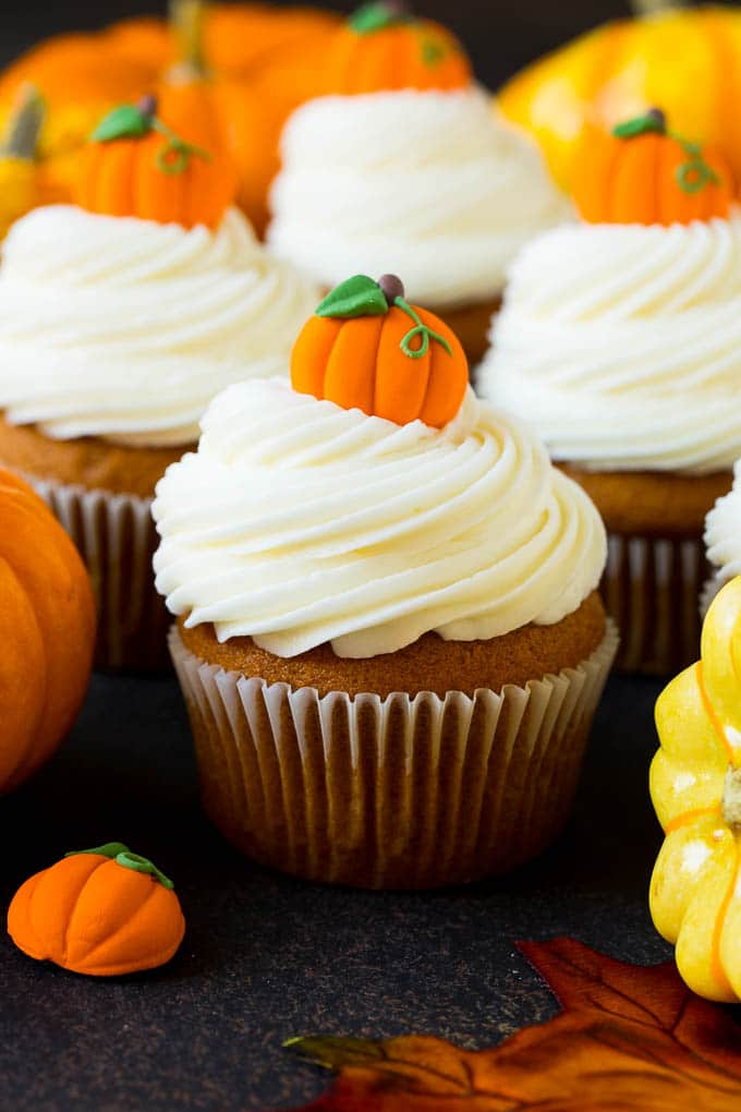 Pumpkin cupcakes topped with cream cheese frosting and candy pumpkins.