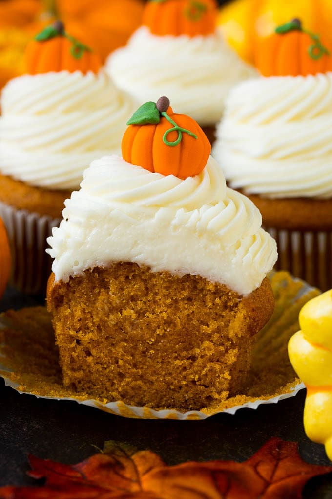 A pumpkin cupcake cut in half, surrounded by fall decorations.