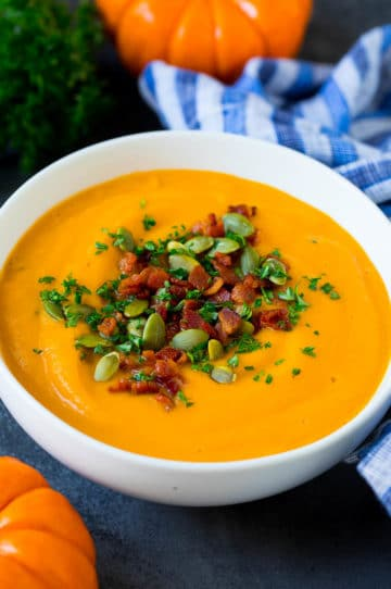A bowl of pumpkin soup topped with bacon and pumpkin seeds.