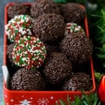 Rum balls coated with sprinkles in a holiday tin.