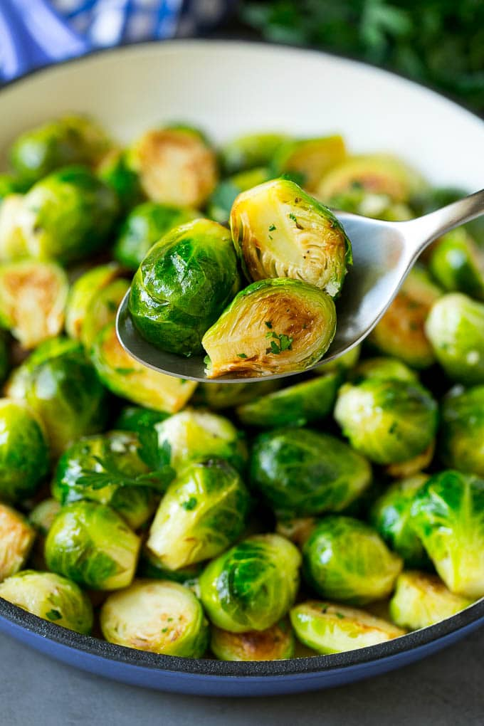 A spoon holding up a serving of cooked brussels sprouts.