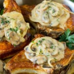A pan of smothered pork chops topped with mushroom and onion gravy.