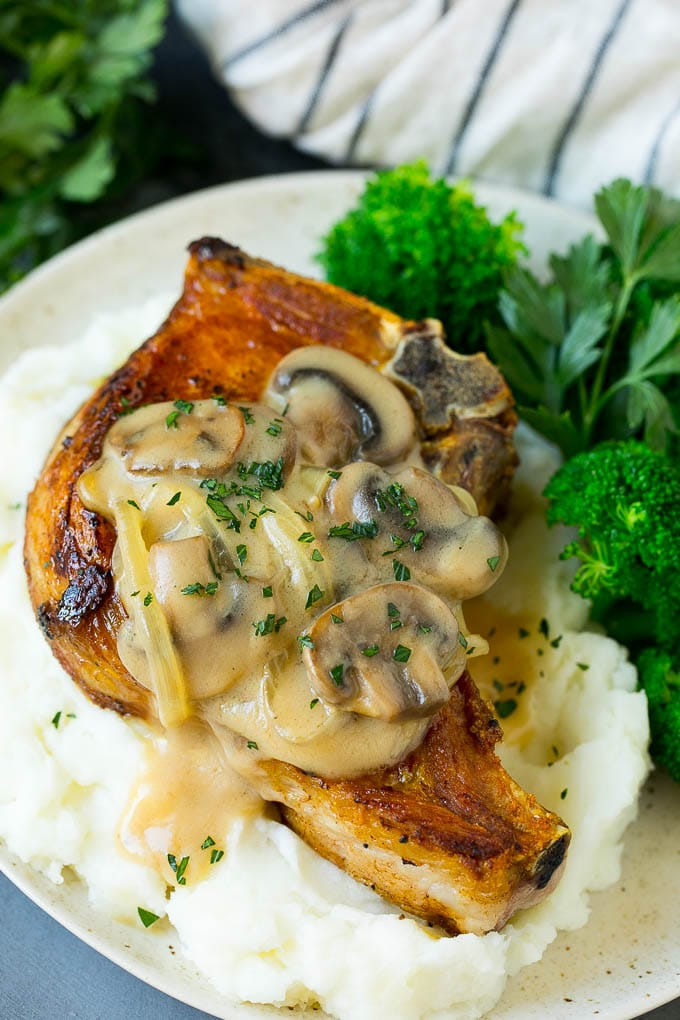 Smothered pork chops served with mashed potatoes and broccoli.