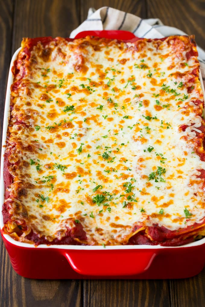 A baked lasagna topped with melted cheese and chopped parsley.