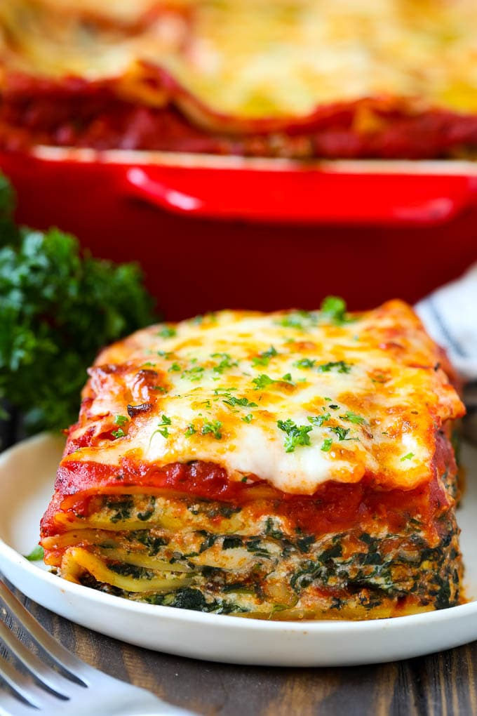 A piece of spinach lasagna on a plate, garnished with chopped parsley.