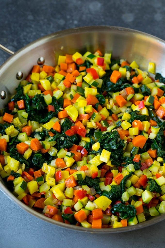 Zucchini, squash, spinach, carrots and peppers in a skillet.