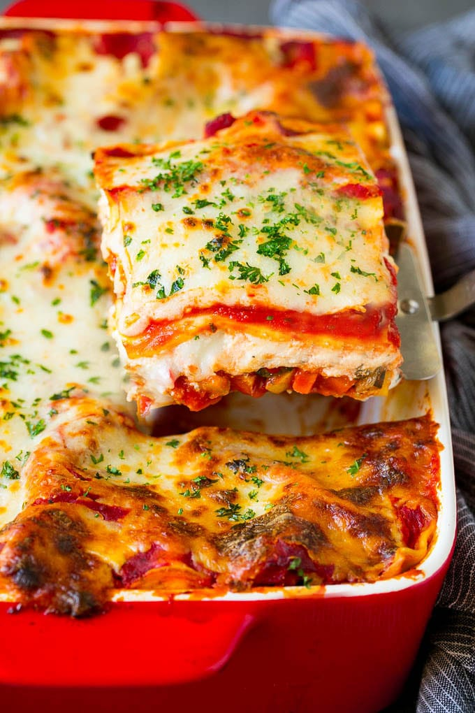 A spatula serving up a portion of vegetable lasagna.