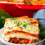 A slice of vegetable lasagna topped with melted cheese and parsley.