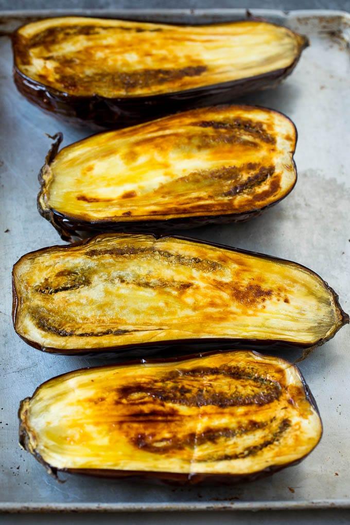 Roasted eggplant halves on a sheet pan.