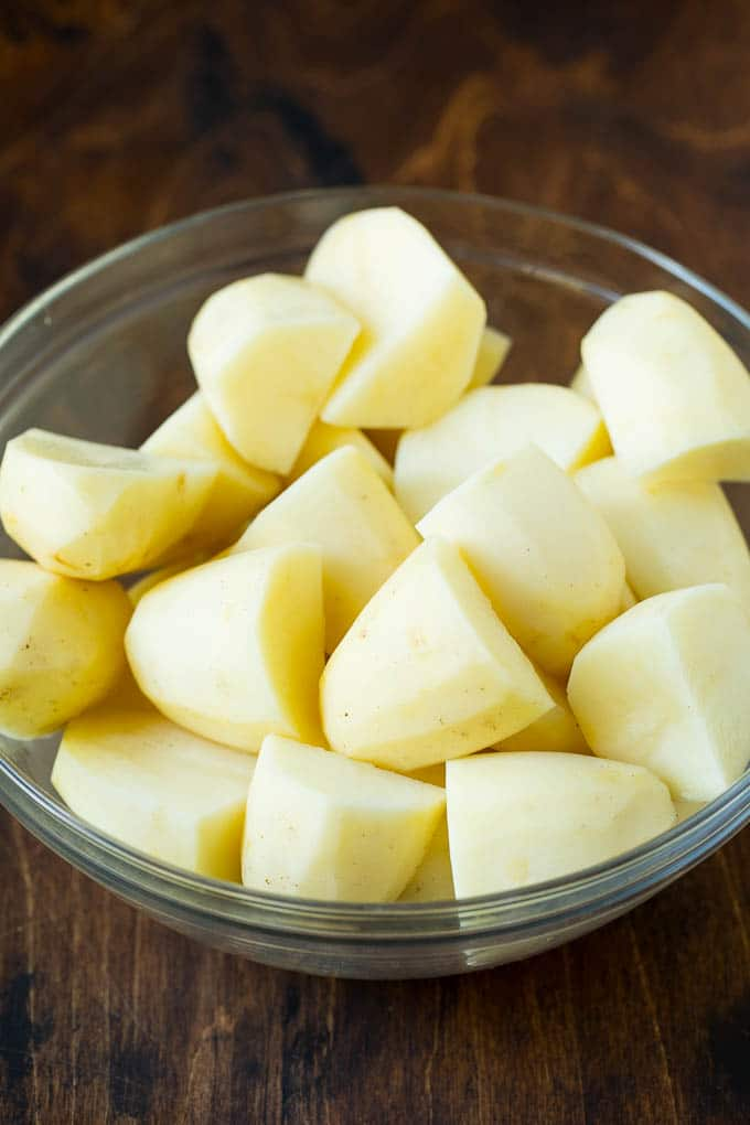 Quartered peeled potatoes in a bowl.