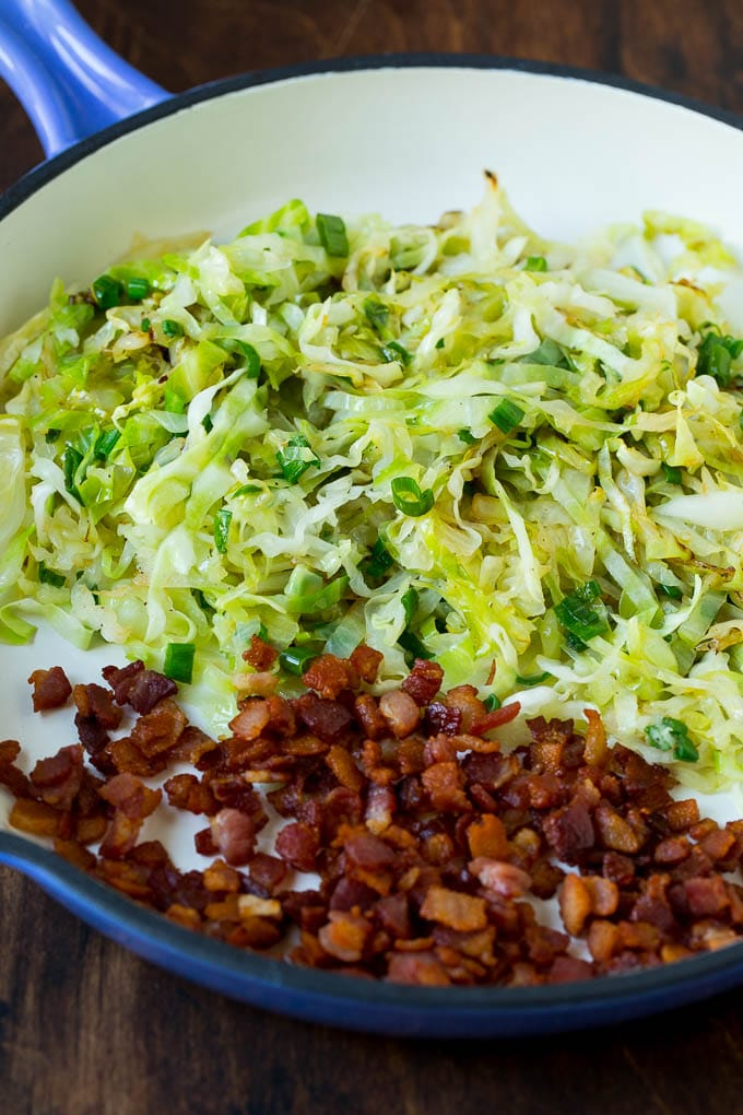 Sauteed cabbage and bacon in a skillet.