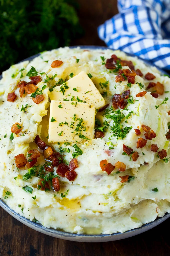 A bowl of colcannon potatoes topped with bacon, parsley and melted butter.
