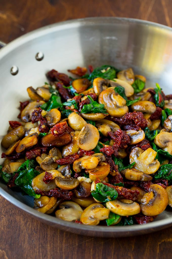 A pan of sauteed mushrooms, garlic, spinach and sun dried tomatoes.